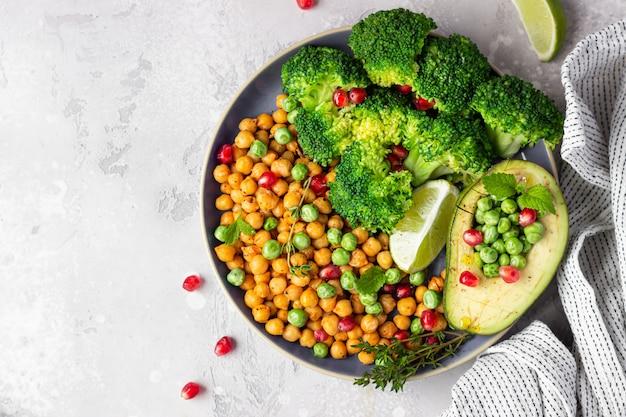 Almuerzo saludable con verduras: brócoli, garbanzos, aguacate, guisantes, granada, lima y menta.