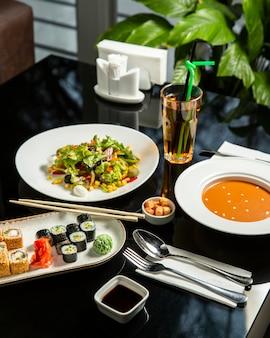 Almuerzo con sopa de lentejas, ensalada de verduras frescas y plato de sushi.