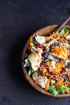 Almuerzo tazón buda con cuscús, pavo, zanahoria, ensalada y sésamo.