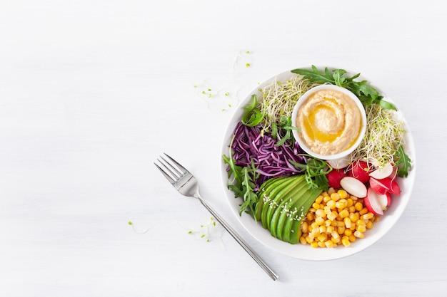 Almuerzo vegano de aguacate y maíz dulce con hummus, repollo rojo, rábano y brotes