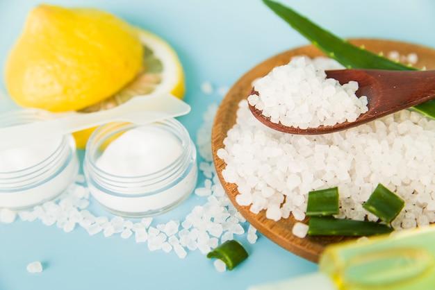 Aloe vera y crema hidratante de limón con sal de roca sobre fondo azul