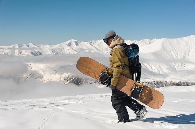 Alpinista masculino camina sobre la nieve con una tabla de snowboard en manos