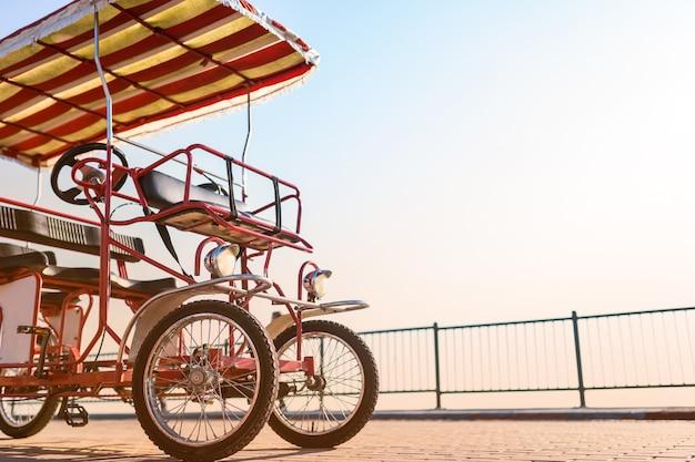 Se alquila bicicleta roja de cuatro ruedas con un toldo y una rueda en el paseo marítimo contra el sol. transporte callejero ecológico.