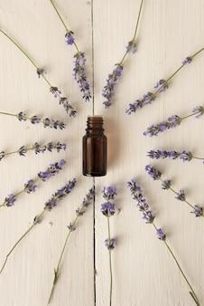 Alrededor del frasco de aceite de lavanda se disponen flores púrpuras fragantes. perfumería de élite. endecha plana