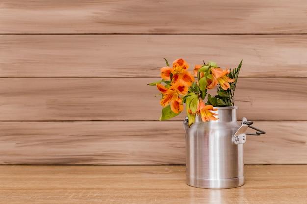 Alstromeria flores y helechos en jarra de leche.
