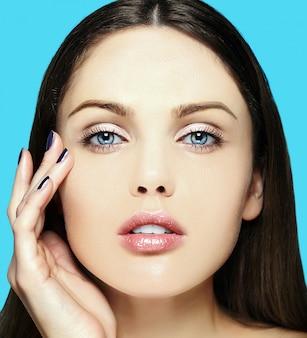 Alta moda look.glamor closeup retrato de belleza de la hermosa modelo de mujer joven caucásica sensual con maquillaje nude con piel limpia perfecta sobre fondo azul