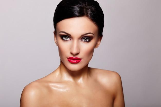 Alta moda look.glamor closeup retrato de la hermosa modelo de mujer joven caucásica sexy con labios rojos, maquillaje brillante, con piel limpia perfecta aislada en gris