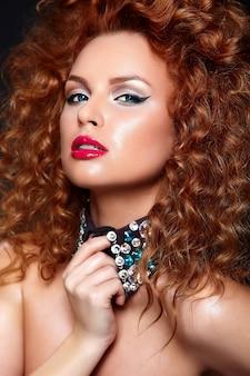 Alta moda look.glamor closeup retrato de hermosa pelirroja sexy modelo caucásica joven con labios rojos, maquillaje brillante, con piel limpia perfecta con joyas aisladas en negro