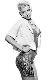 Alta moda look.glamor closeup retrato de hermosa sexy caliente elegante rubia joven modelo con maquillaje brillante de pelo corto con tatuaje