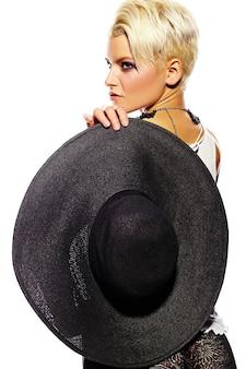 Alta moda look.glamor closeup retrato de hermosa sexy elegante caucásica joven modelo con maquillaje moderno brillante con cabello corto con sombrero en mano