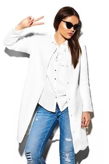 Alta moda look.glamor closeup retrato de hermosa sexy elegante morena mujer de negocios joven modelo en chaqueta de abrigo blanco paño hipster en jeans