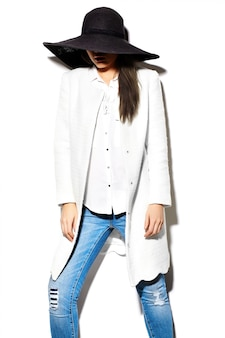 Alta moda look.glamor closeup retrato de hermosa sexy elegante morena negocio joven modelo en bata blanca chaqueta hipster tela en jeans en sombrero