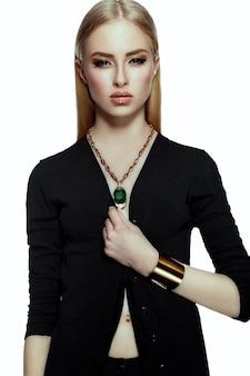 Alta moda look.glamor closeup retrato de hermosa sexy elegante rubia joven modelo con maquillaje amarillo brillante con piel limpia perfecta con joyas de oro en tela negra