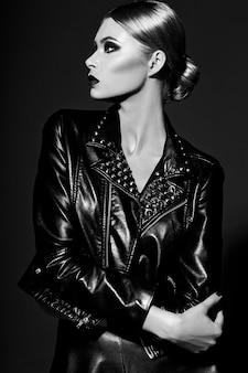 Alta moda look.glamor closeup retrato de hermosa sexy elegante rubia joven modelo con maquillaje brillante con labios rojos con piel limpia perfecta en tela negra
