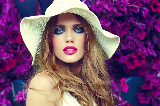 Alta moda look.glamor closeup retrato de hermosa sexy elegante rubia joven modelo con maquillaje brillante y labios rosados con piel limpia perfecta en sombrero cerca de flores de verano