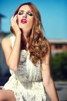 Alta moda look.glamor closeup retrato de hermosa sexy elegante rubia joven modelo con maquillaje brillante y labios rosados con piel limpia perfecta en vestido blanco de verano en la ciudad