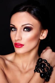 Alta moda look.glamor closeup retrato de hermosa sexy modelo caucásica joven con labios rojos, maquillaje brillante, con piel limpia perfecta aislada en negro