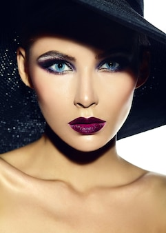 Alta moda look.glamor closeup retrato de hermosa sexy modelo elegante joven con maquillaje brillante con labios rojos con piel limpia perfecta en tela casual en sombrero