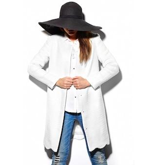 Alta moda look.glamor closeup retrato de hermosa sexy morena elegante hipster mujer joven modelo en chaqueta blanca y gran sombrero negro