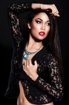 Alta moda look.glamor closeup retrato de hermosa sexy morena elegante modelo caucásica joven con maquillaje brillante, con labios rojos, con piel limpia perfecta con joyas en tela negra