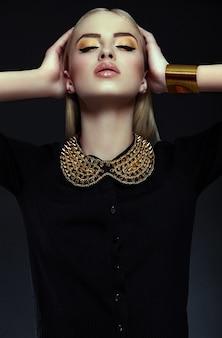 Alta moda look.glamor closeup retrato de hermosa sexy rubia elegante joven modelo con maquillaje amarillo brillante con piel limpia perfecta con joyas de oro en tela negra