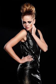 Alta moda look.glamor retrato de hermosa sexy elegante caucásica joven mujer modelo en vestido negro con maquillaje brillante y peinado
