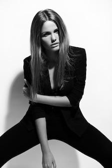 Alta moda look.glamor retrato de hermosa sexy elegante modelo caucásica joven en ropa negra posando junto a la pared