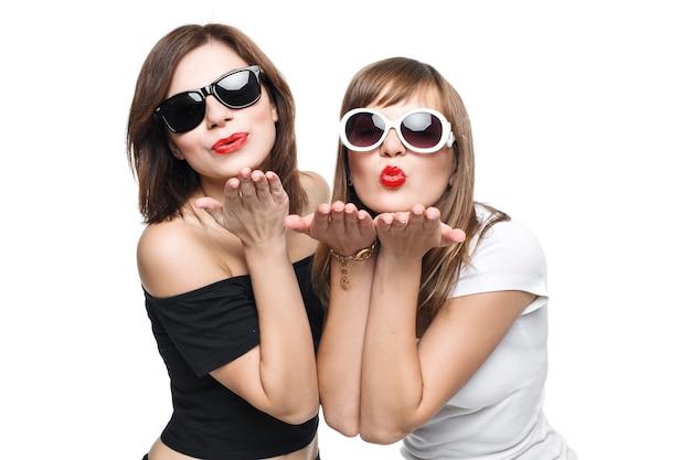 Alta moda. modelo de mujeres jóvenes con estilo glamoroso con labios rojos en un blanco y negro brillante ropa hipster y gafas de sol envían un beso