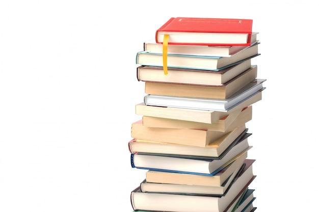 Alta pila de diferentes libros aislados. libro rojo con marcador amarillo en la parte superior del fondo de la pila