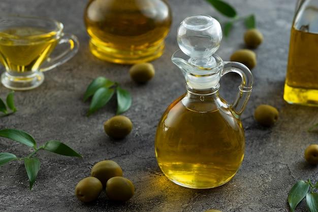 Alta vista de botellas llenas de aceite de oliva sobre fondo de mármol