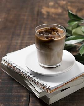 Alta vista delicioso café en taza en la pila de cuadernos