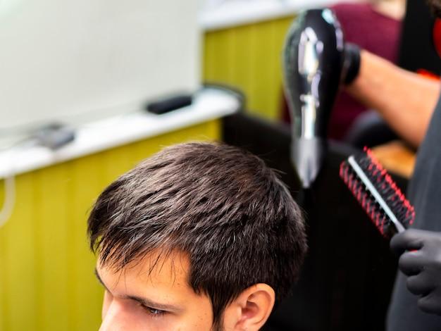 Alta vista del estilista que seca el cabello del cliente