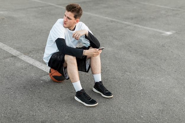 Alta vista hombre sentado en una pelota de baloncesto