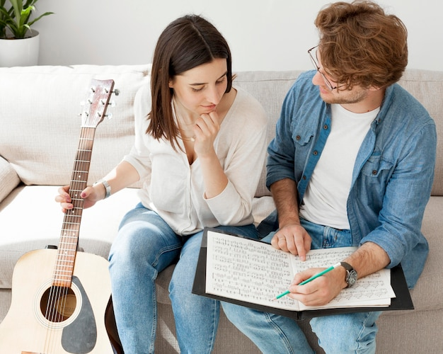 Alta vista joven estudiante aprendiendo guitarra