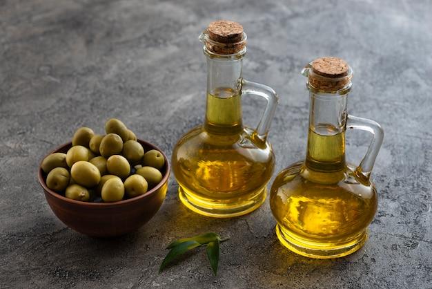 Alta vista de lindas botellas de aceite de oliva y un tazón de aceitunas