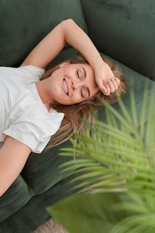 Alta vista mujer sentada en un sofá y sonriendo