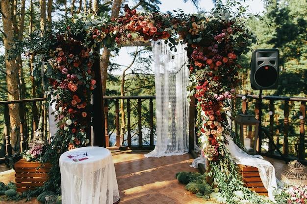 Altar de bodas hecho de spearworts coloridos y cortina blanca