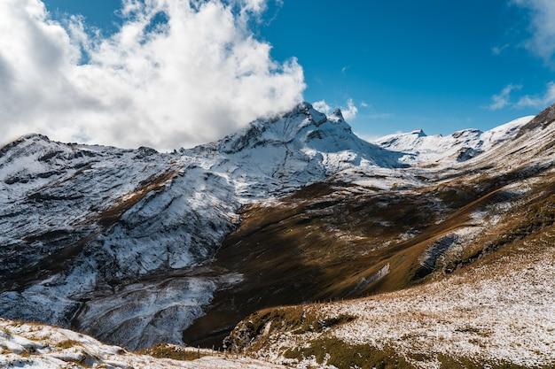 Altas montañas rocosas cubiertas de nieve bajo un cielo azul claro en suiza
