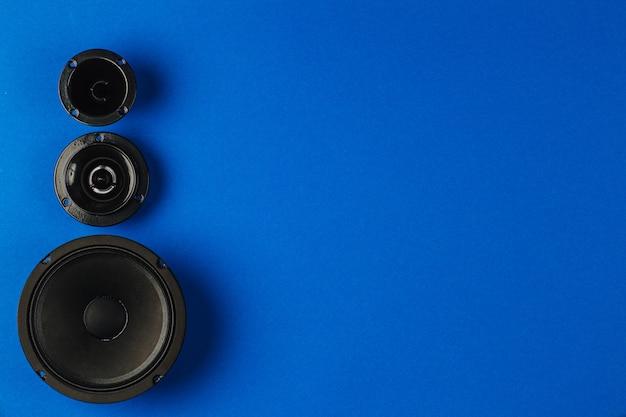 Altavoces de coche de audio para coche, altavoz de graves y altavoz de rango medio se encuentran en una fila sobre un fondo azul.