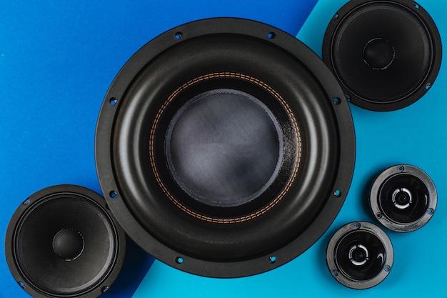 Altavoces de coche de audio de coche subwoofer negro sobre un fondo azul claro de cerca