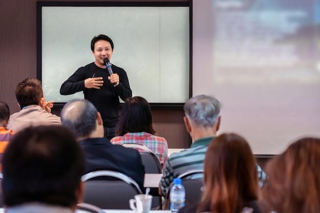 Altavoz asiático o conferencia con traje casual en el escenario frente a la sala que presenta