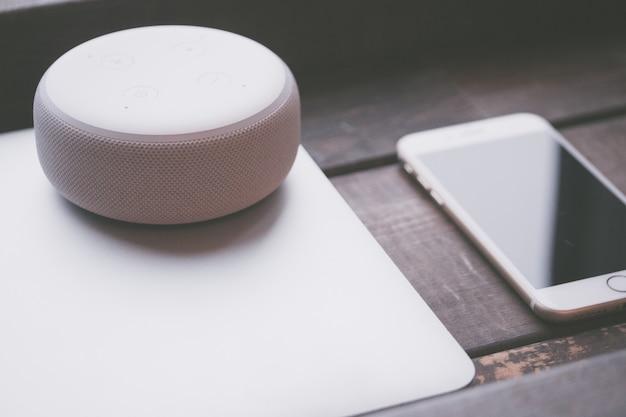 Altavoz bluetooth redondo blanco grande en una computadora portátil gris y un teléfono inteligente en el lateral