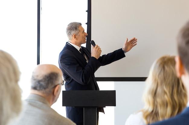 Altavoz de negocios con micrófono apuntando con la mano a la pizarra en blanco frente a la audiencia, conferencia, concepto de seminario