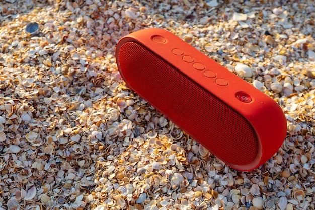 Altavoz rojo inalámbrico en la playa del mar. concepto para los amantes de la música de vacaciones. musica en todas partes