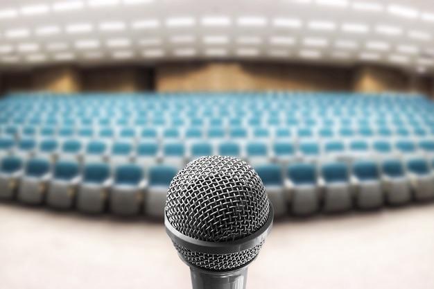 Altavoz de voz de micrófono sobre la foto borrosa de la sala de seminarios vacía