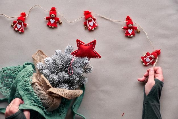 Alternativa verde navidad, año nuevo concepto. vista plana, vista superior en papel artesanal. ¡celebra con un árbol falso sin matar a un árbol real! árbol de navidad de plástico en bolsa de malla, juguetes ecológicos sin plástico.