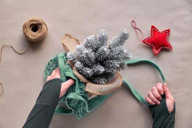 Alternativa verde navidad, año nuevo concepto. vista plana, vista superior en papel artesanal. ¡celebra con un árbol falso sin matar a un árbol real! manos tomando plástico árbol de navidad con estrella roja de bolsa de malla.