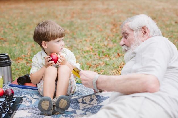 Alto ángulo abuelo y nieto en picnic