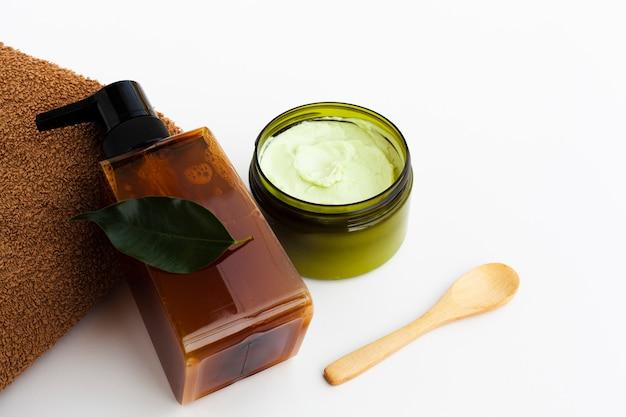 Alto ángulo de aceite esencial y crema sobre fondo blanco.