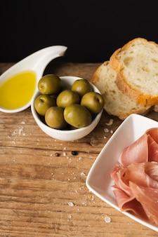 Alto ángulo aceitunas pan y jamón en tabla de cortar